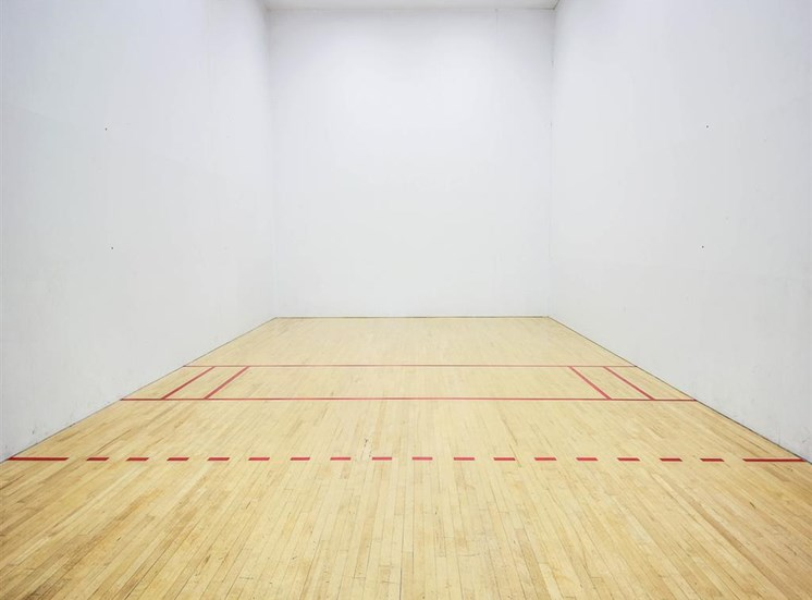 Indoor Racquetball Court with Wood Flooring and White Walls