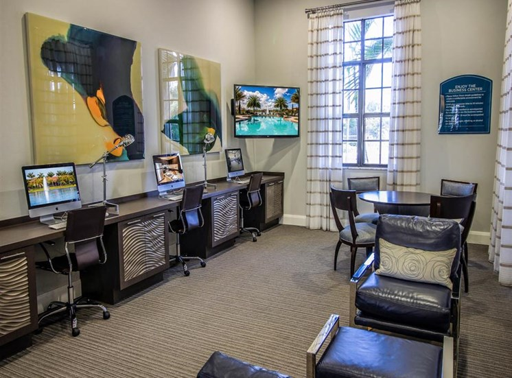 Business Center with Macs on Built in Desk, Under Art Next to Mounted TV with Tables and Chairs