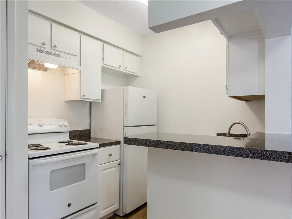 Kitchen with White Cabinets and Appliances with Black Counters and Breakfast Bar