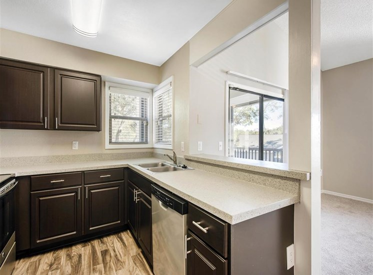 Kitchen with Brown Cabinets Stainless Steel Appliances and Grey Counters and Breakfast Bar