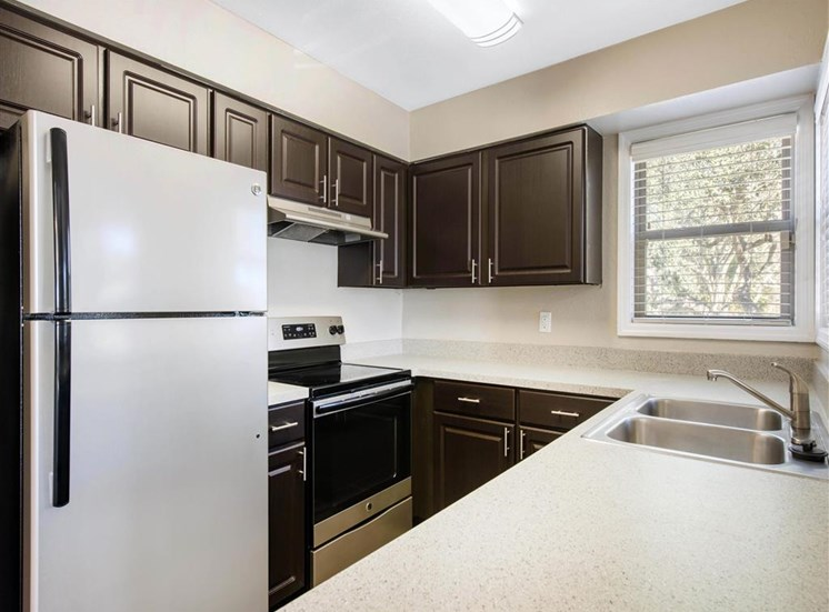 Kitchen with Brown Cabinets Stainless Steel Appliances and Grey Counters and Window