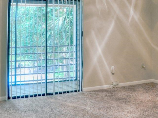 Carpeted Living Room with Ceiling Fan and  Sliding Glass Door with Vertical Blinds