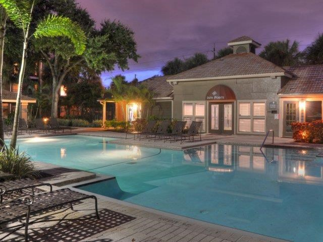 Leasing Office Exterior with Swimming Pool with Sun Deck Surrounded by Palm Trees