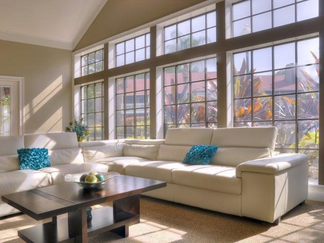 Clubhouse Seating Area with Large Windows Behind White Couch with Wood Coffee Table