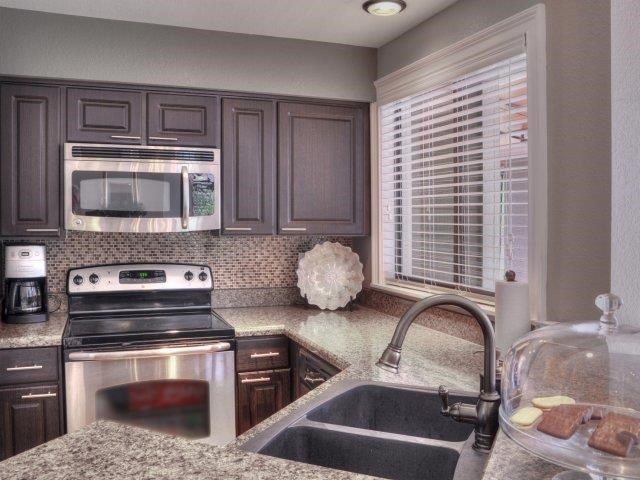 Clubhouse Kitchen with Brown Cabinets and Stainless Steel Appliances with Large Window