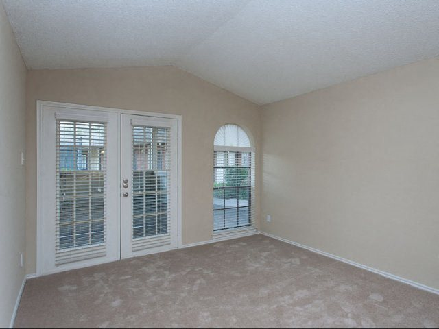 Wall to wall carpet with arched windows, vaulted ceilings, and french doors going to balcony/patio