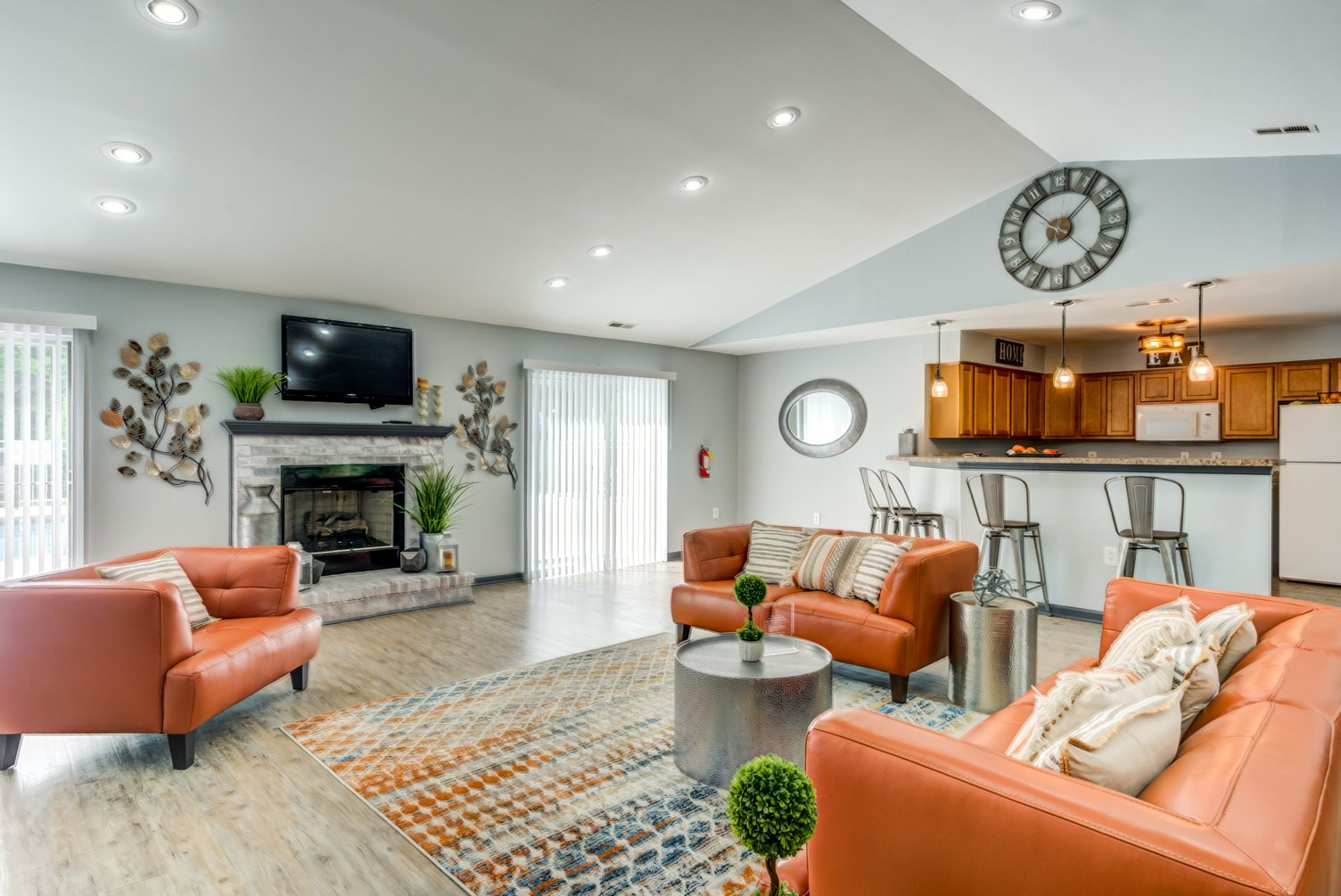 Clubhouse interior with vaulted ceilings, hardwood style flooring, colorful rug, and leather chairs