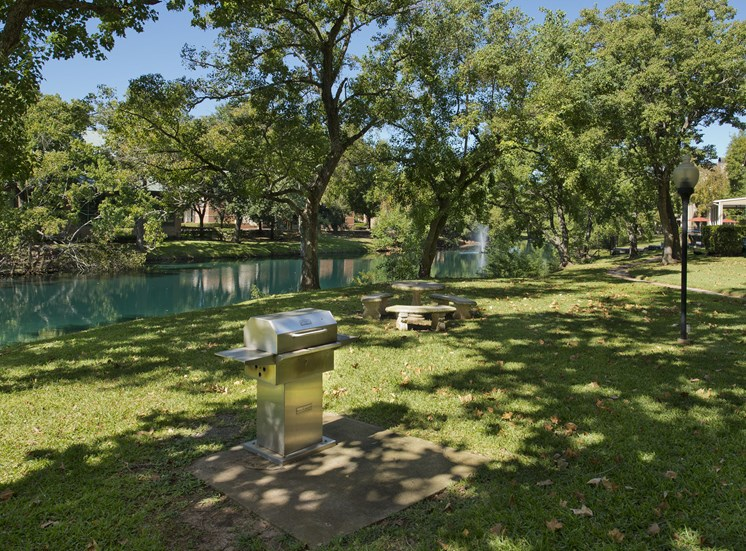 Waterfront Grill and Stone Picnic Table in Grassy Courtyard with Trees
