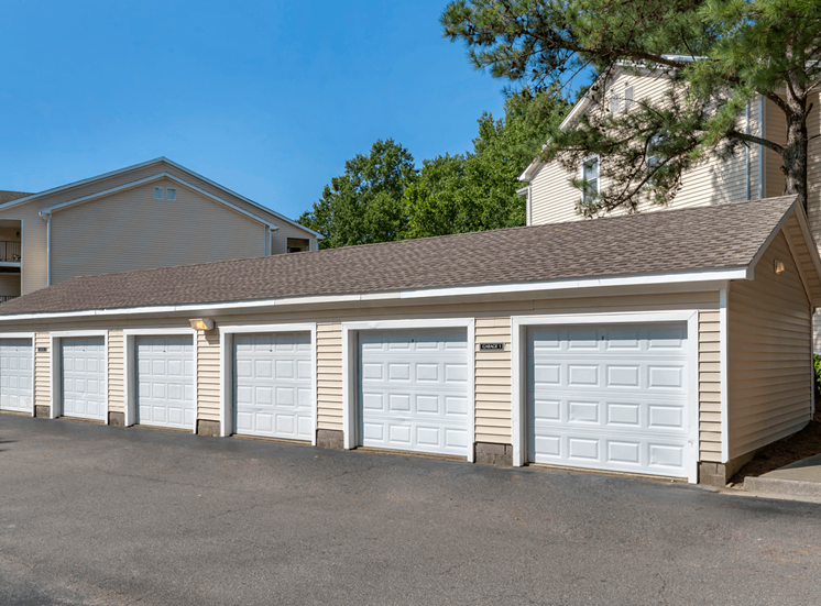 Detached Garages Next to Parking Lot with Trees in the Background