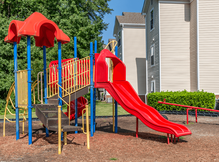 Red Yellow and Blue Playground with Red Seesaw with Building Exterior and Treeline in the Background