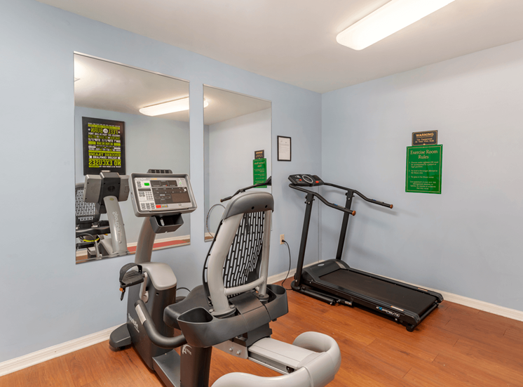 Fitness Center with Exercise Equipment and Mirror Accents on Wall