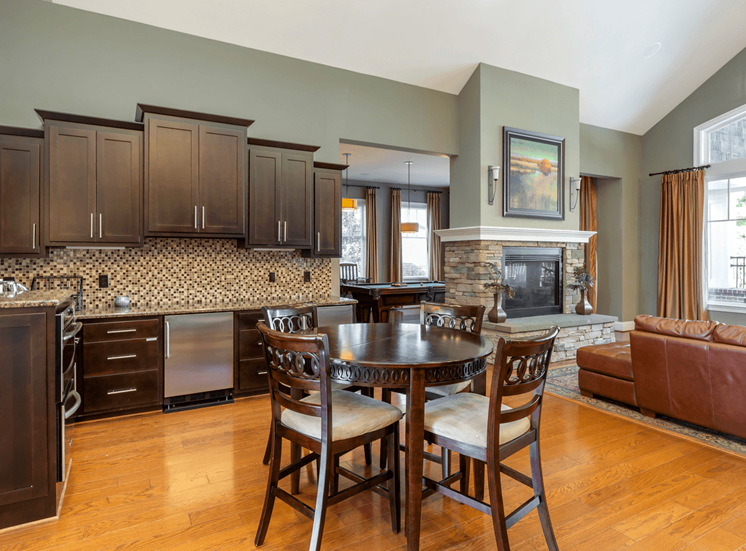 Clubhouse Kitchen with Dining Table, Dark Wood Cabinets and Stainless Steel Appliances