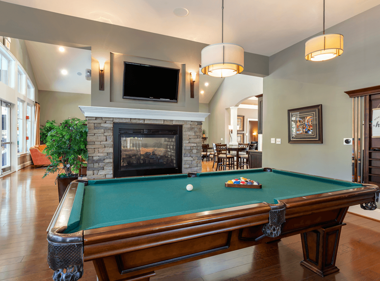 Billiards room with large flat screen tv mounted above a fireplace with a Billiards table