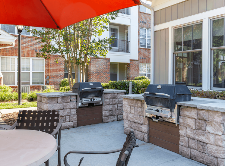 Outdoor grilling stations with tables on a patio