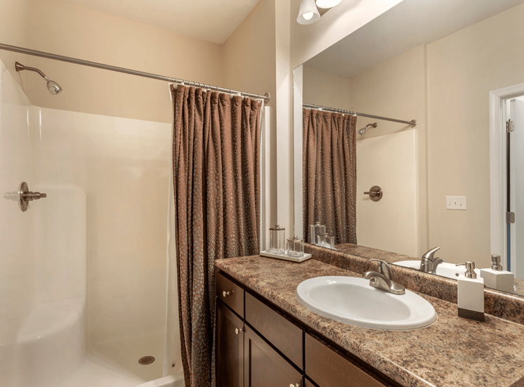 Model Bathroom with Walk in Shower and Brown Shower Curtain