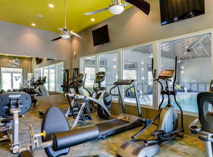 Fitness Center with Exercise Equipment and Windows to Pool Area