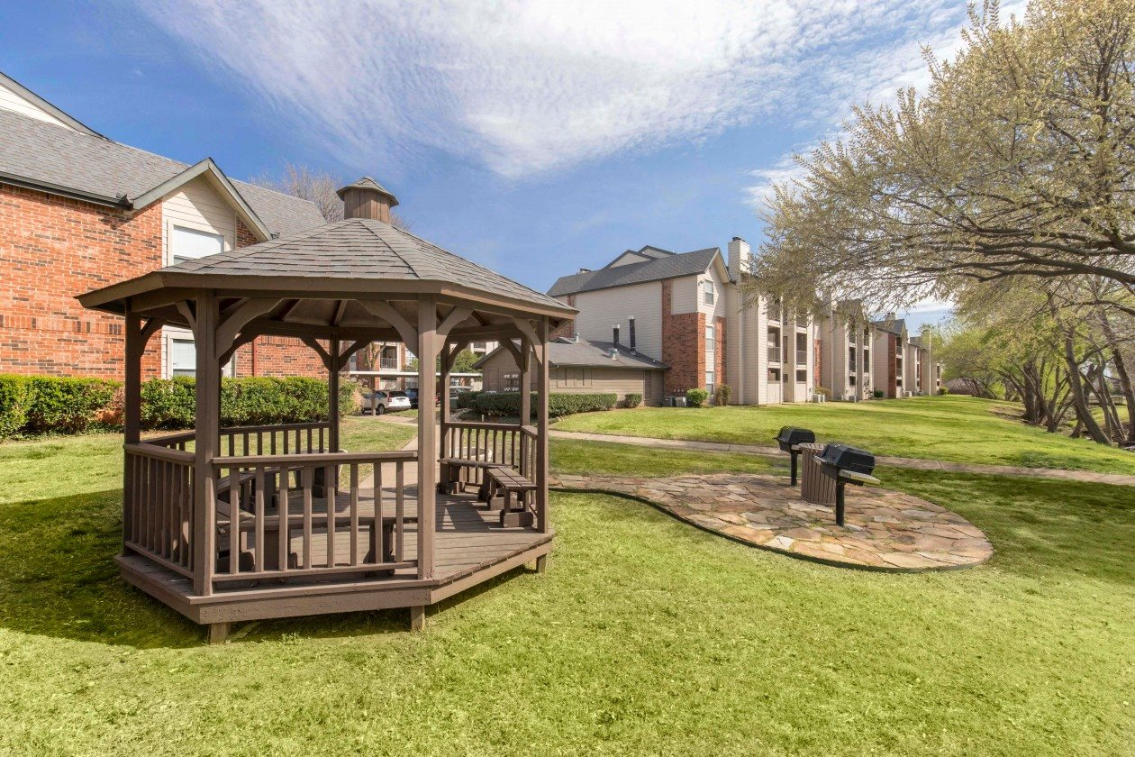 Gazebo outdoors, blue skies, spacious greenbelt, with building exterior in the background