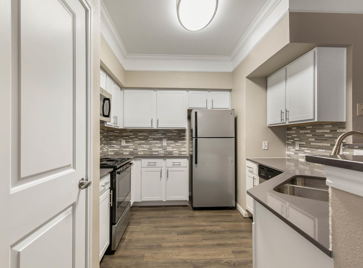 Model Kitchen with White Cabinets, Stainless Steel Appliances, Grey Counters and Breakfast Bar