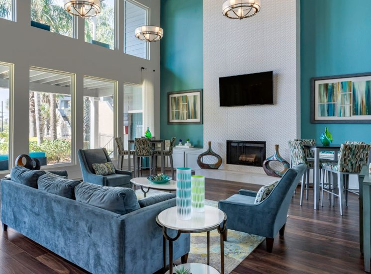 Clubhouse interior with teal green accent walls, wall-mounted television, and blue furniture