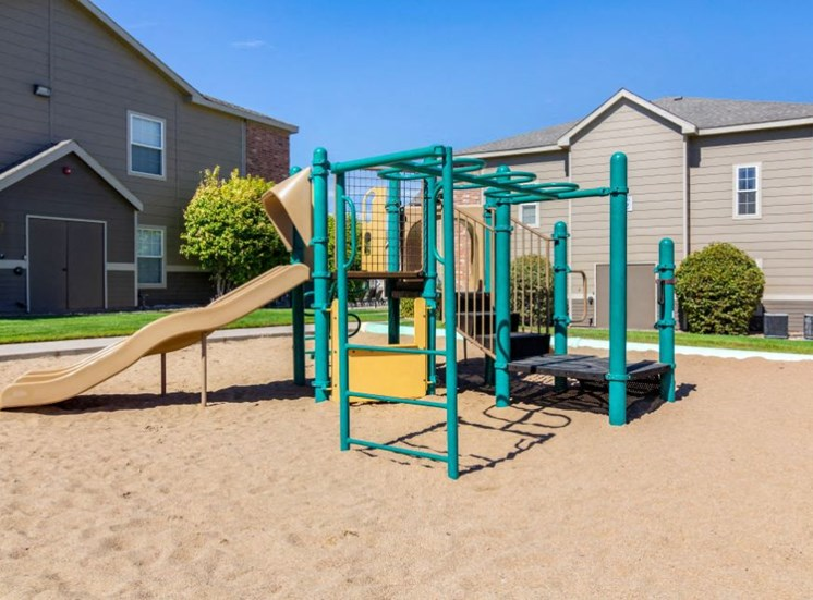 Green and Yellow Playground on Sand with Building Exteriors in the Background