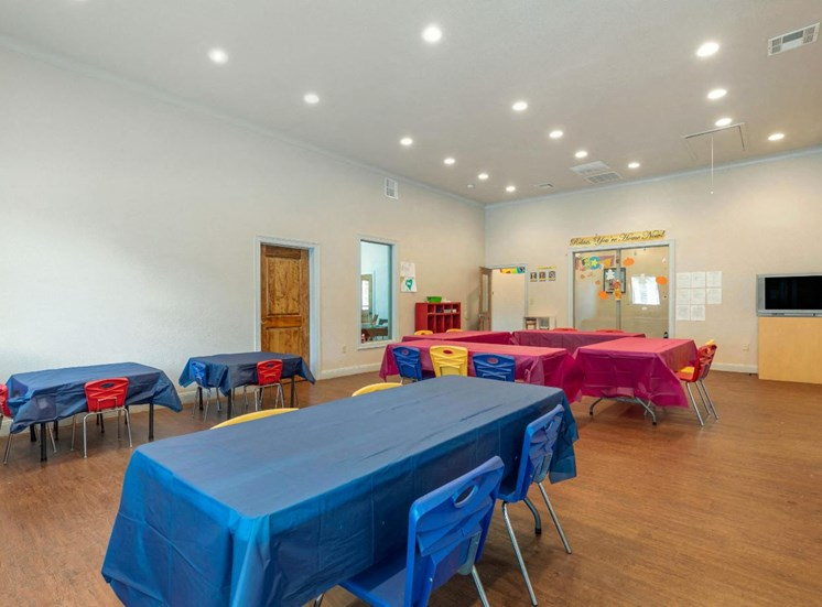 Resident activity room with tables and chairs