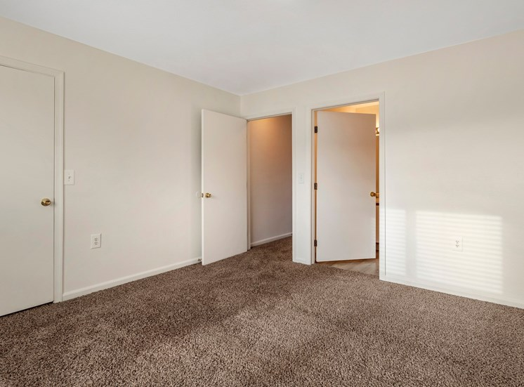 bedroom with wall to wall carpet and doors to closet, bathroom and hallway