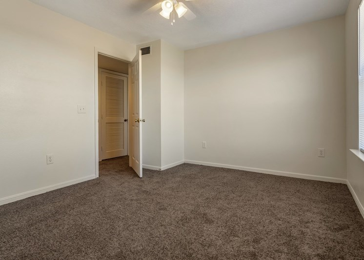 Bedroom with en-suite bathroom, ceiling fan, and carpet flooring