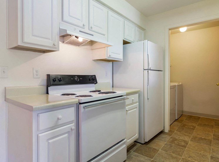 Fully Equipped Kitchen with White Appliances, White Cabinets and Grey Counters Next to Utility Closet with Washer and Dryer
