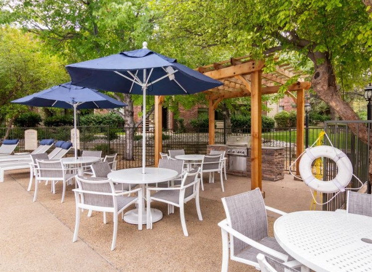 Grilling Station at the pool with Picnic Area with tables and umbrellas, with some lounge