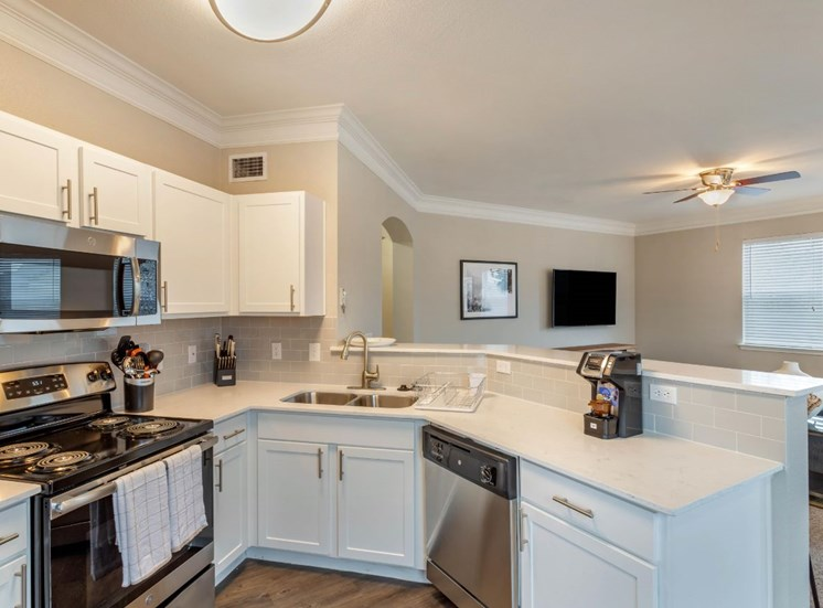 Model Kitchen with Stainless Steel Appliances, White Counters, White Cabinets and Decorations