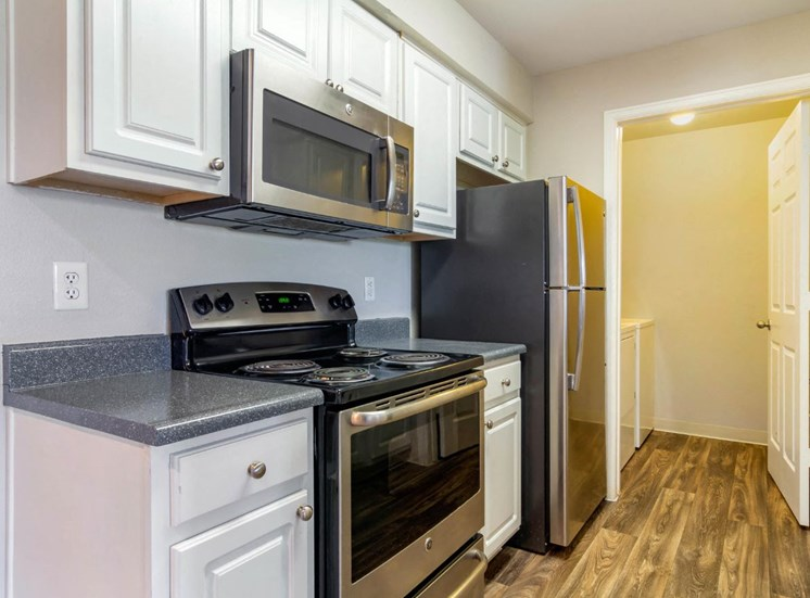Fully Equipped Kitchen with Brushed Nickel Appliances, White Cabinets, Grey Counters and Utility Closet with Washer and Dryer
