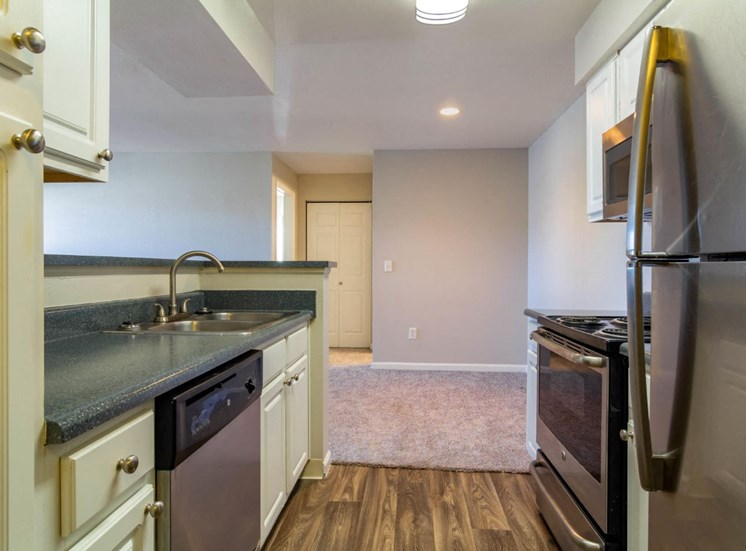 Fully Equipped Kitchen with Brushed Nickel Appliances, White Cabinets, Grey Counters Next to Carpeted Dining Room