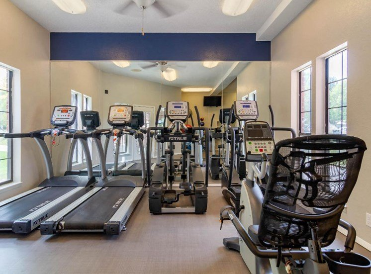 Fitness center with equipment and a mirror wall.
