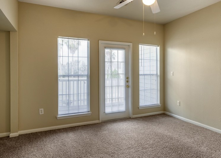 Living room with view of patio door and two large windows placed on either side