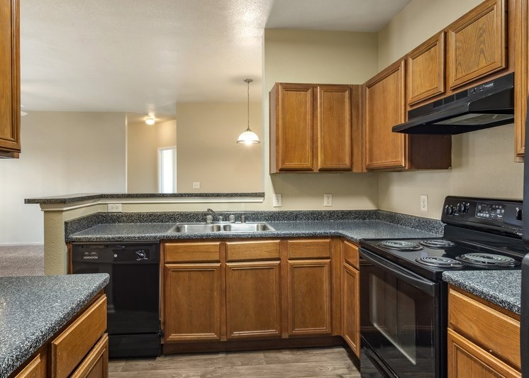 Fully equipped kitchen with black appliances and wooden cabinetry
