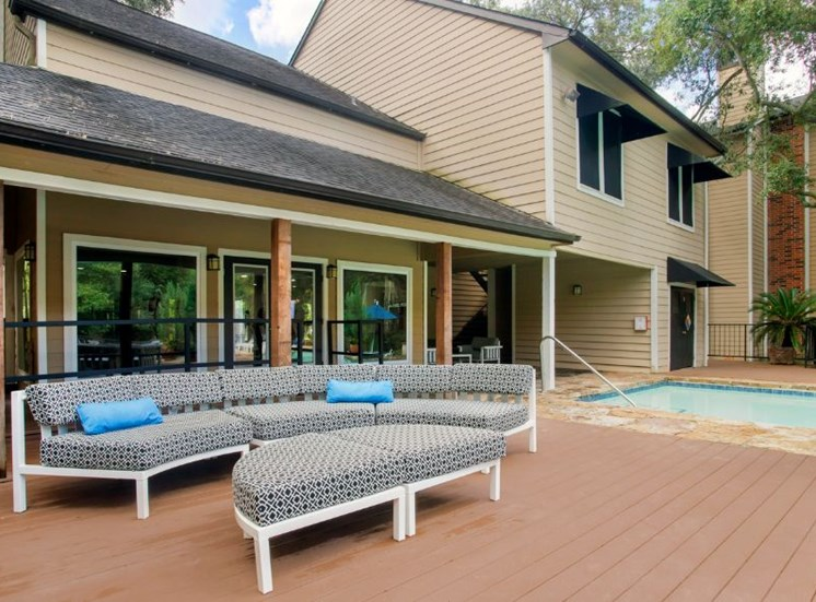Pool side gray lounge chairs with blue accent pillows