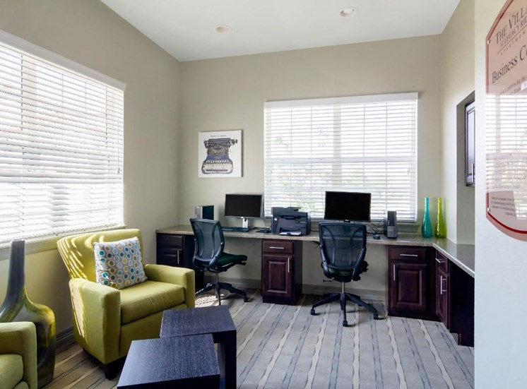 Resident Business Center with Built in Desk with Computers and Rolling Chairs Next to Bright Green Armchairs