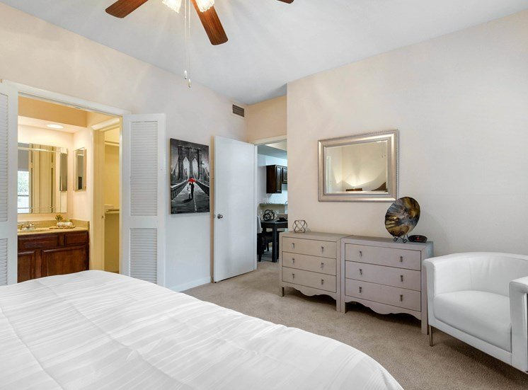 Bedroom with a ceiling fan, wall to wall carpet, white bedding, white dresser, and a mirror hanging on the wall