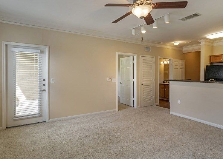 Living room with breakfast bar, ceiling fan, and carpeted flooring