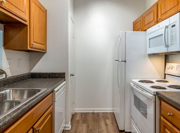 Fully equipped kitchen with wooden cabinetry, hardwood style flooring, and white appliances