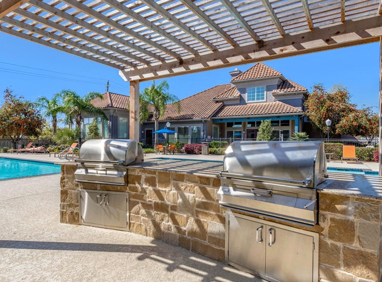 Poolside Summer Kitchen with Outdoor Grilling Under Pergola