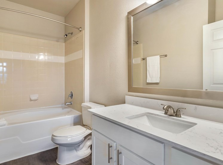 Model Bathroom with White Counters and White Cabinets Next to Tiled Shower with Bathtub