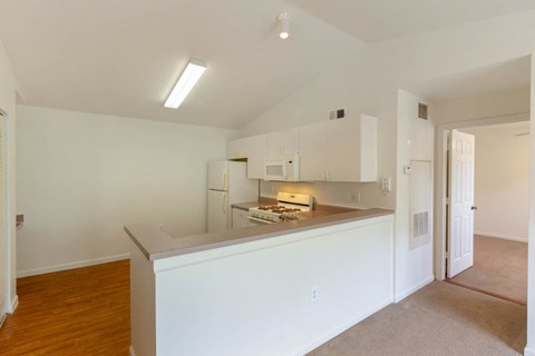 Large Open Kitchen with Mauve Counters White Appliances and Cabinets with Carpeted Living Room and Bedroom Barely Visible