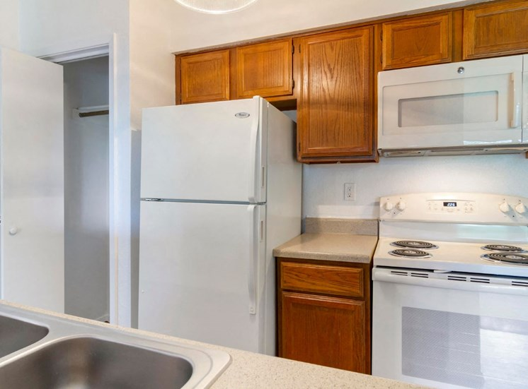 Fully Equipped Kitchen with White Appliances. Cabinets above all the appliance with a microwave.