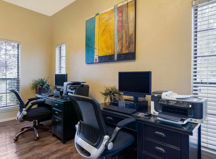 Bright Resident Business Center with Art Mounted Between Two Windows and Two Black Desk with Computers Printers and Rolling Chairs
