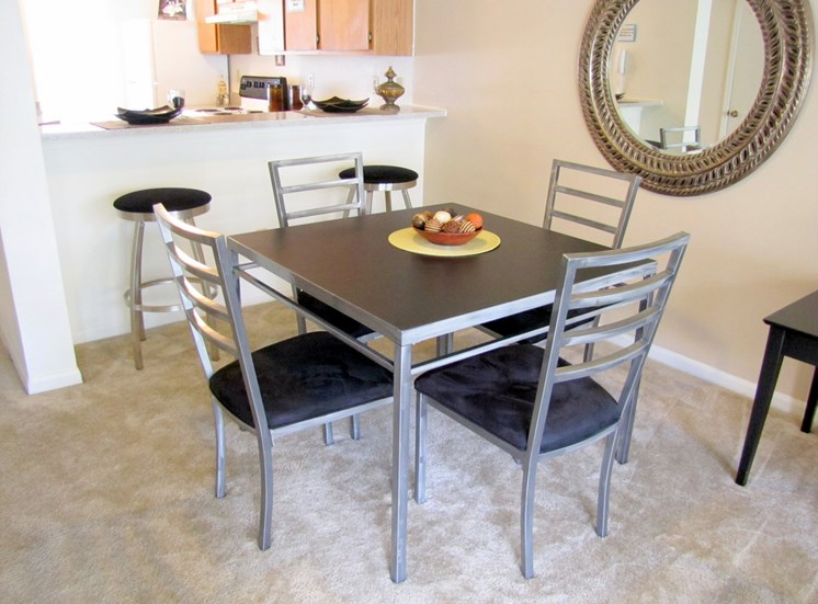Dining room with mirrored accent wall, dining room table with chairs and kitchen breakfast bar with stools in the background