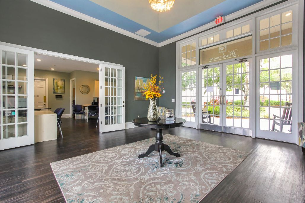 Clubhouse Foyer with a Table in the Middle with A Vase and Flowers on it Hardwood Floors Large Windows and Open Doors Leading to Clubhouse Seating Area
