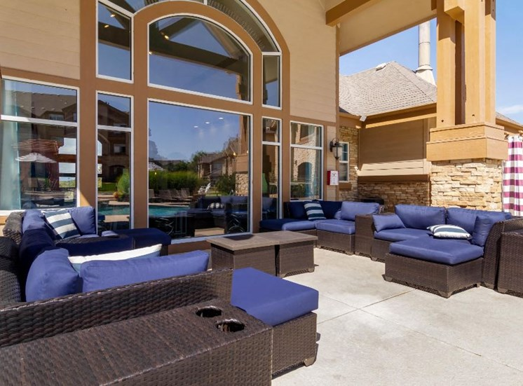 Outdoor Seating Area with Cushioned Couch and Armchairs Next to Windows