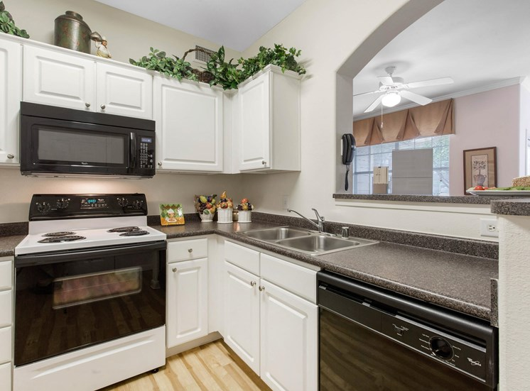 Fully Equipped Model Kitchen with White Cabinets Grey Counters and Decorations