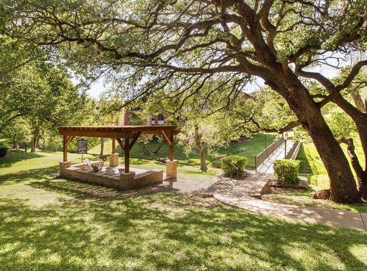 Outdoor green valley with large green trees, a gazebo with seating, and a bridge walk way